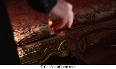 businessman drinking brandy and puts the glass on the coffee table