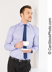 Businessman drinking coffee. Cheerful young man in formalwear standing near the window and holding a cup