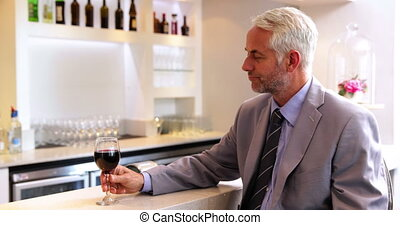 Businessman drinking glass of red wine