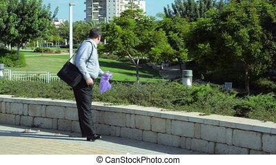 Businessman drinking in park