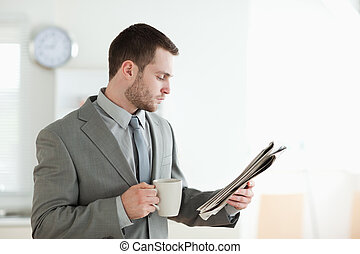 Businessman drinking tea while reading the news