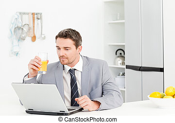 Businessman drinking while he is looking at his laptop