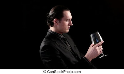 businessman drinking wine on black