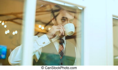 Businessman drinks coffee