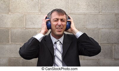 Businessman Earmuffs Hearing Pain - Man wearing a business...