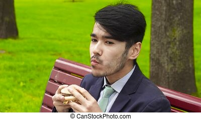 Businessman eating fresh tasty burger - Businessman eating...