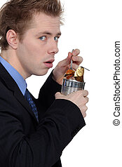 Businessman eating from a tin