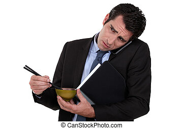 Businessman eating Japanese food whilst telephoning