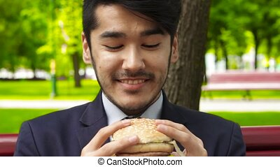 Businessman eating tasty burger sitting in the summer park