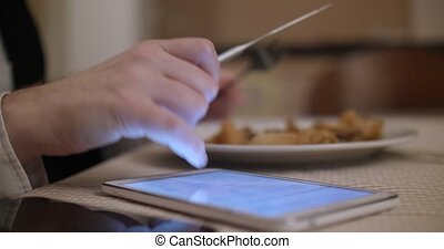 Businessman eats at a restaurant and uses a tablet Closeup