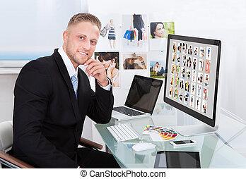 Businessman editing photographs - Businessman sitting at his...
