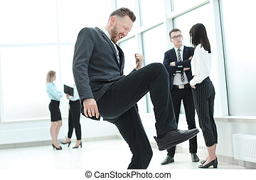 businessman enjoys his success standing in the hall of the business center.