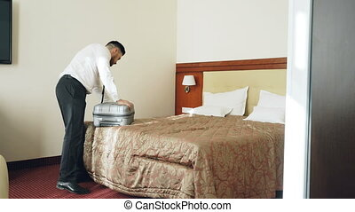 Businessman entering hotel room unpacking his suitcase put on jacket after check-in. Travel, business and people concept