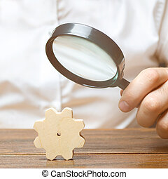 Businessman examines a wooden gear through a magnifying glass. A cog from a big business machine. Every little thing is important. study and analysis of business processes and subjects Research