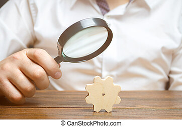 Businessman examines a wooden gear through a magnifying glass. study and analysis of business processes and subjects. A cog from a big business machine. Every little thing is important. Research