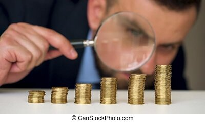 Businessman examines in a magnifying glass columns of coins...