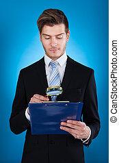 Businessman Examining Document On Clipboard
