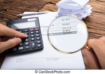 Businessman Examining Invoice With Magnifying Glass At Table