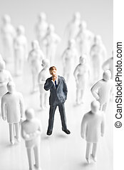 Businessman figurine surrounded by white, faceless figurines