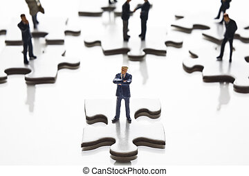 Businessman figurines placed with puzzle pieces
