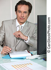 Businessman filling out a form at his desk