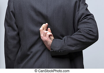 Businessman fingers crossed behind his back