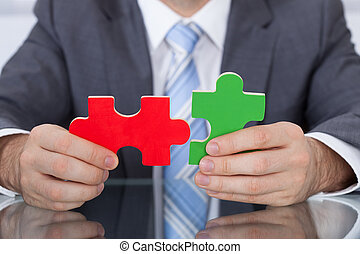 Businessman Fitting Two Puzzle Pieces Together