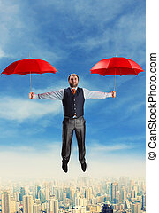 Businessman flying with umbrellas