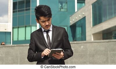 Businessman from asia using tablet for work standing in...