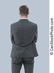 Businessman from the back - looking at something over a gray bac