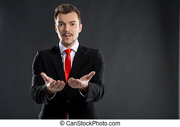 Businessman. Frustrated young men stretching out his hands while standing isolated on black