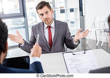 businessman gesturing during job interview, business concept