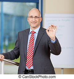 Businessman Gesturing Ok Sign In Office