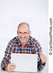Businessman Gesturing Thumbs Up While Using Laptop At Desk