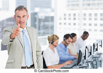 Businessman gesturing thumbs up with executives using computers