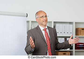 Businessman Gesturing While Giving Presentation In Office