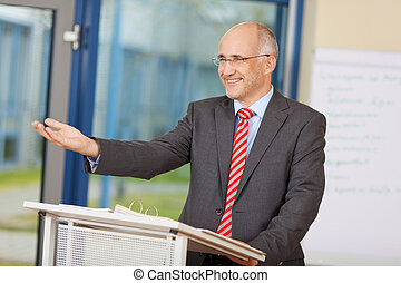 Businessman Gesturing While Standing At Podium - Happy ...
