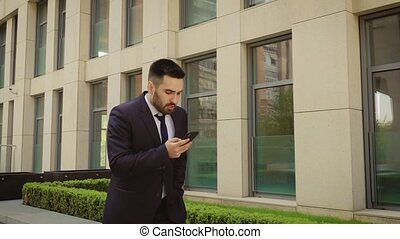 Businessman gets bad news from smartphone conversation on a way to office and become angry because of it