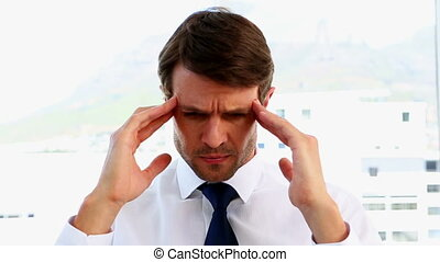 Businessman getting a headache in the office