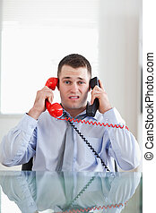 Businessman getting overextended by the telephone