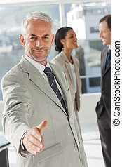 Businessman giving a handshake with colleagues behind...