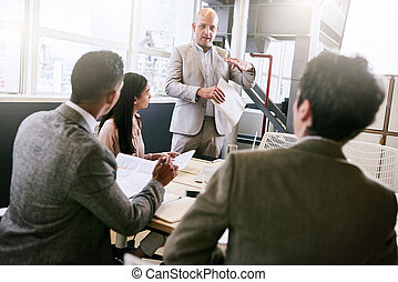 Businessman giving a presentation to colleagues in conference room