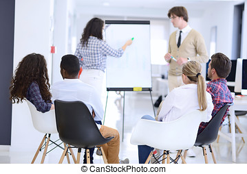 Businessman giving a presentation to his colleagues at work standing in front of a flipchart