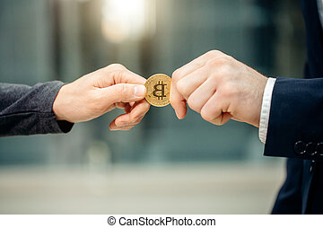 Businessman giving bitcoin to another person. hands exchanging cryptocurrency