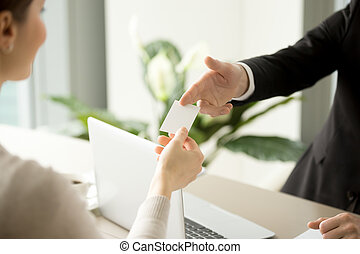 Businessman giving business card to businesswoman
