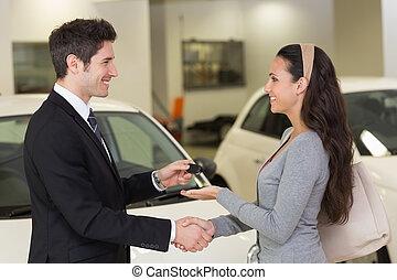 Businessman giving car key while shaking a customer hand