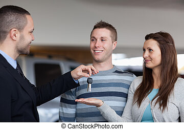 Businessman giving car keys to a woman