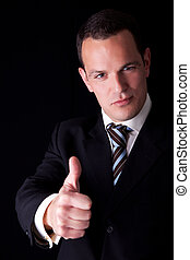 businessman giving consent, with thumb up, isolated on black...