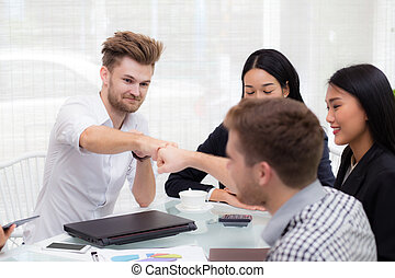 businessman giving fist bump after business achievement in meeting room - teamwork concept.