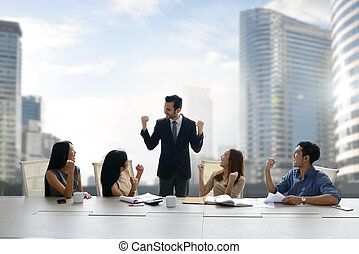 Businessman giving inspiration talk to colleagues in a team meeting